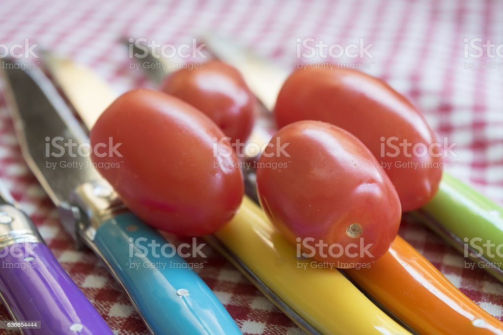 san marzano tomatoes on colored knives stock photo