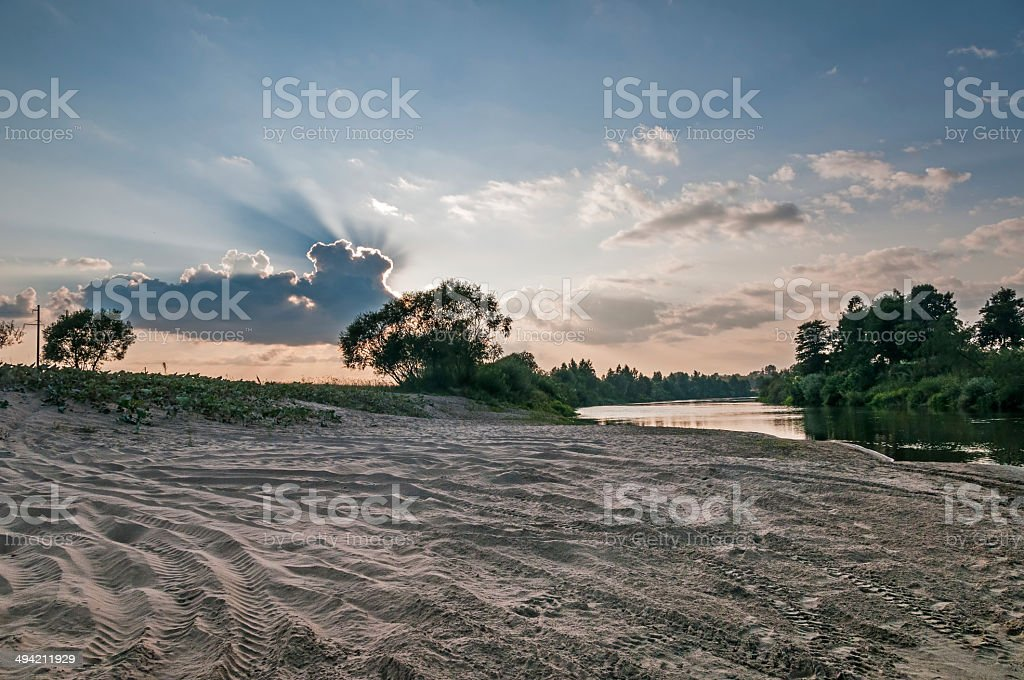 Sand beach and bush against sunbeams behind cloud background royalty-free stock photo