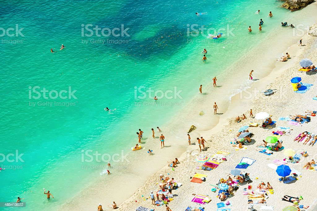Sand beach with people on the hot summer day. stock photo