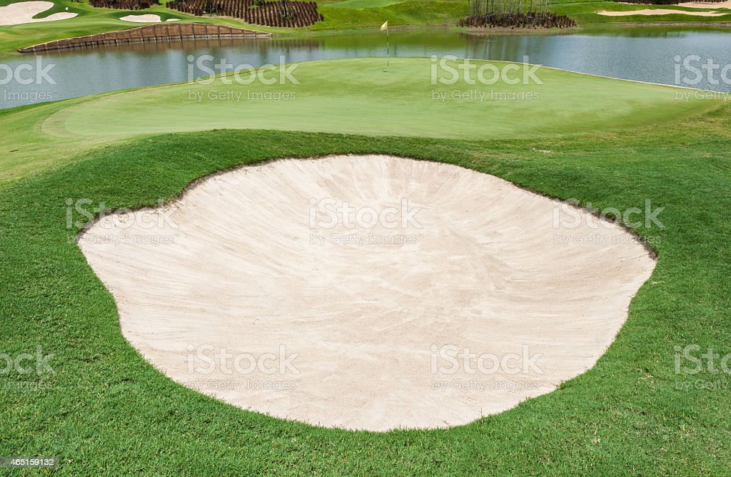 Sand bunker and clear lake on the beautiful golf course stock photo