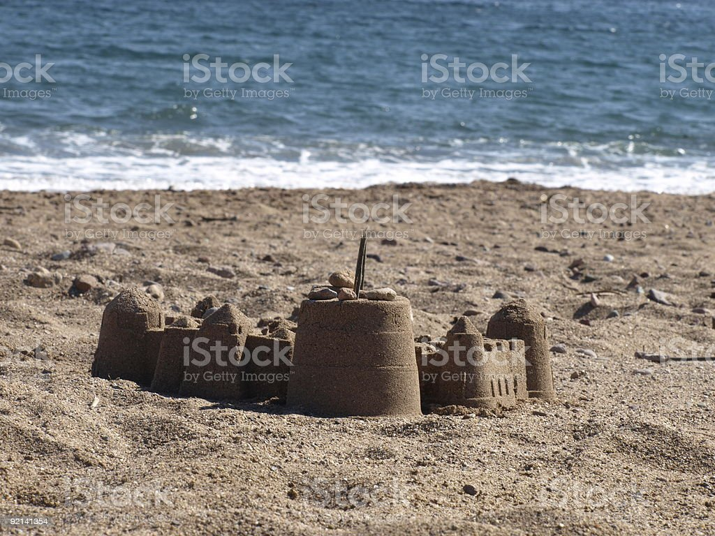 sand castle on the beach with ocean in background royalty-free stock photo