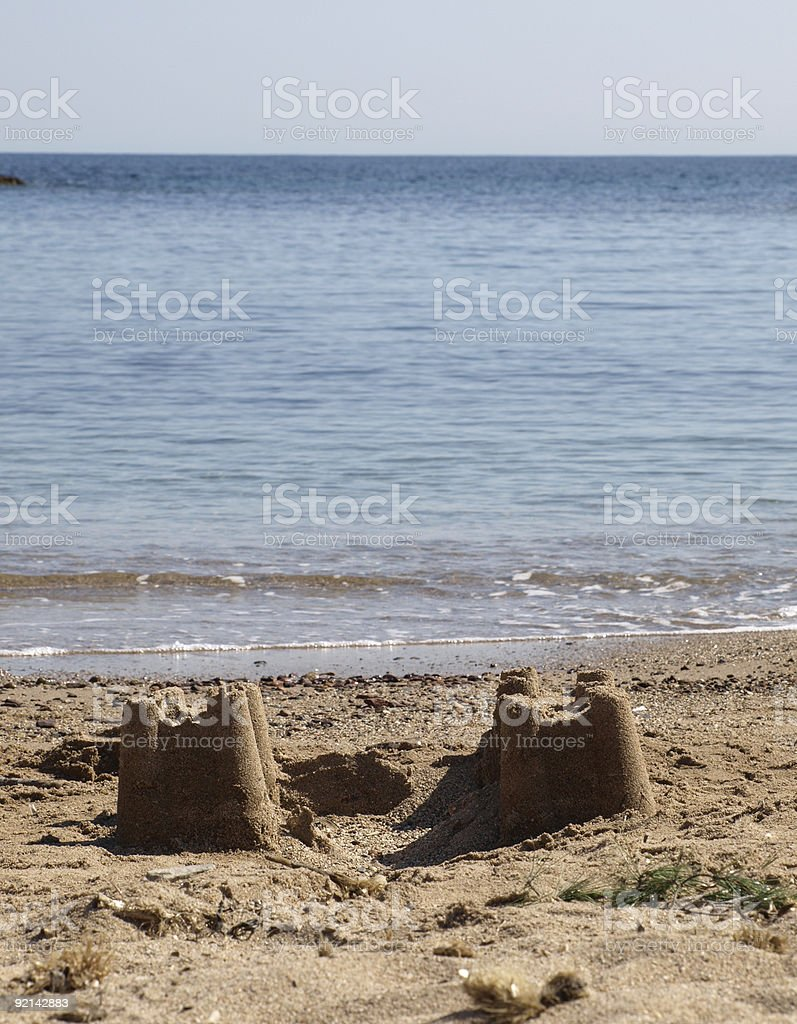 sand castle on the beach with two towers an ocean royalty-free stock photo