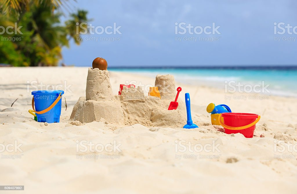 Sand castle on tropical beach and kids toys stock photo