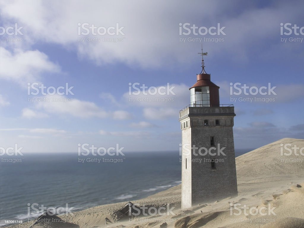 Sand covered landscape with old lighthouse and sea in background royalty-free stock photo