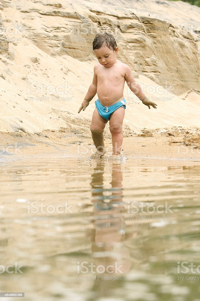 sand dirty baby walking on the beach. stock photo