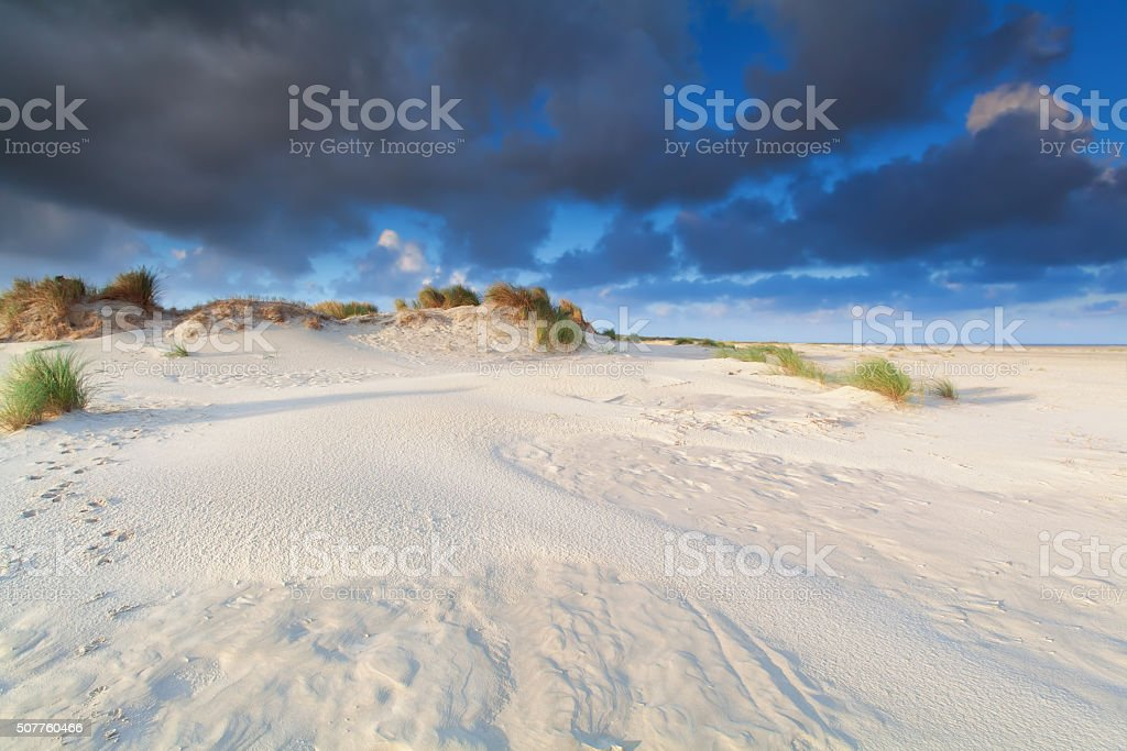 sand dune and blue sky by sea stock photo