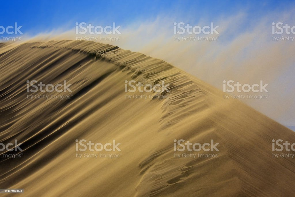 A sand dune in a sandstorm with sand blowing off the top stock photo