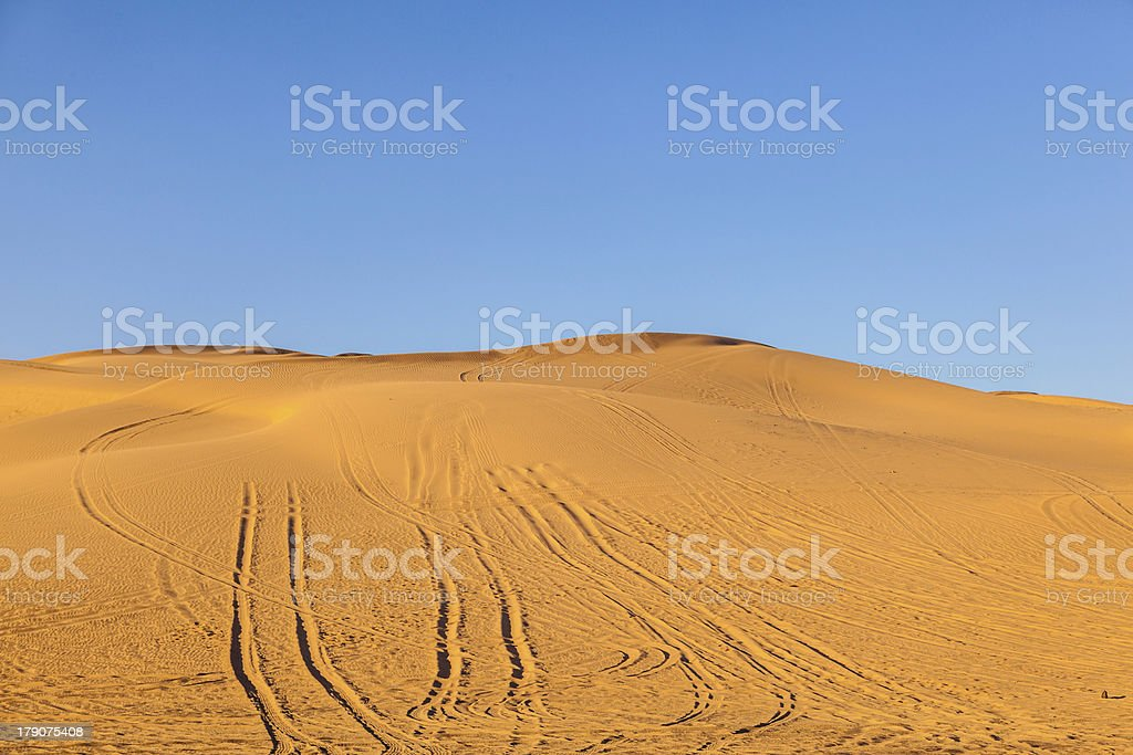 sand dune in the desert with marks of cars royalty-free stock photo
