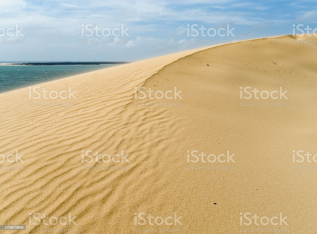 Sand dune near ocean water under a blue sky stock photo