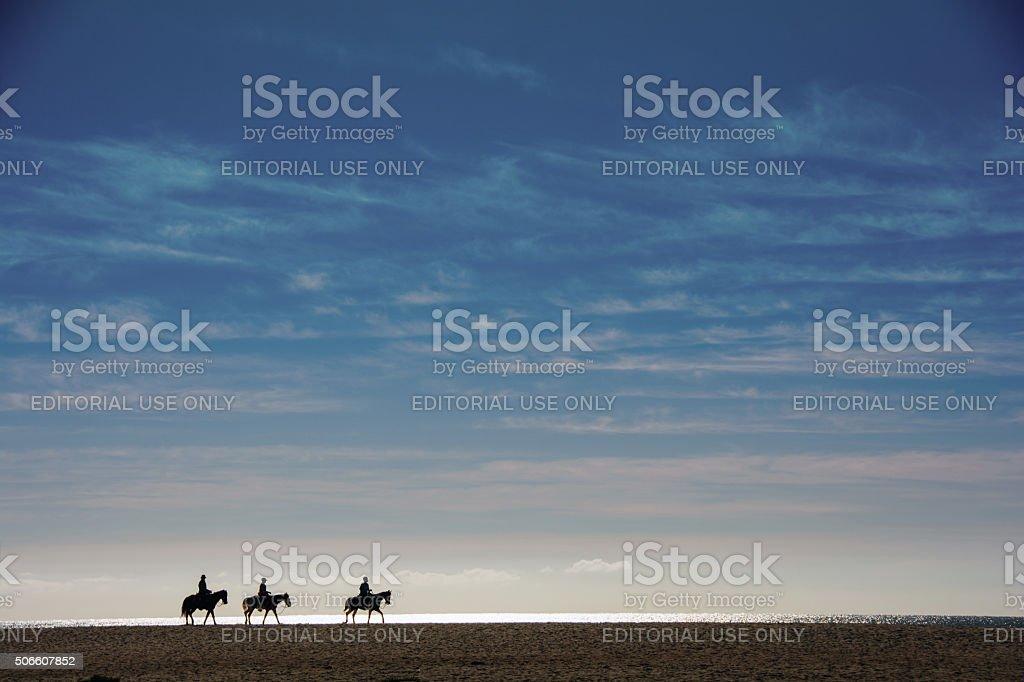Sand Dune Riders at  Sunset- sunset silhouette stock photo