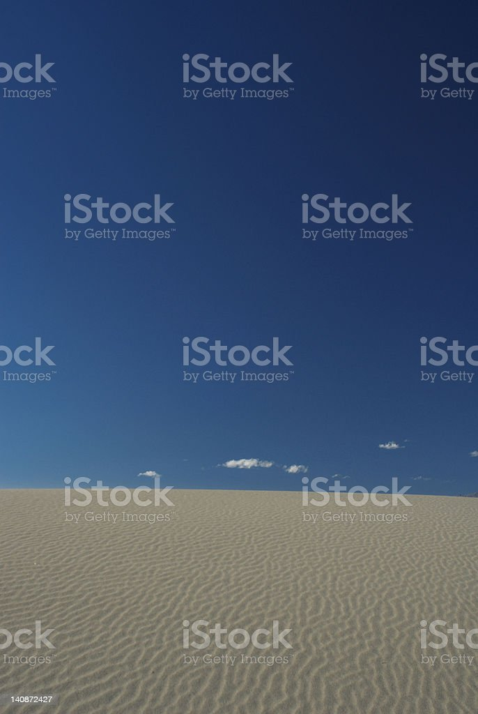 Sand dune under blue sky stock photo