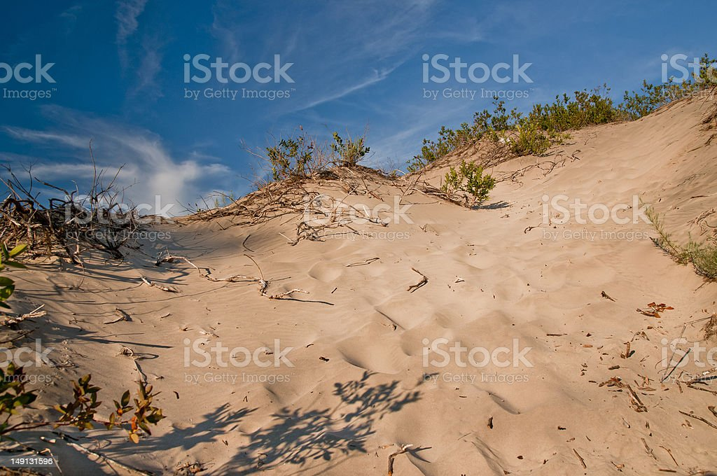 sand dune with wispy clouds in background stock photo