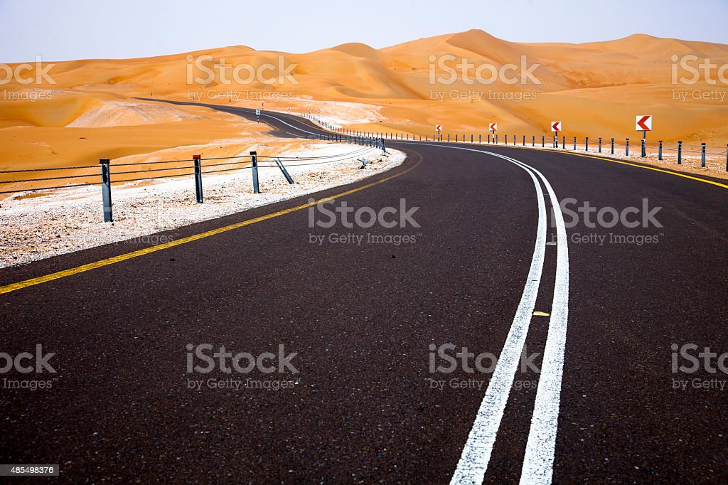 Sand dunes and winding road in Liwa, United Arab Emirates stock photo