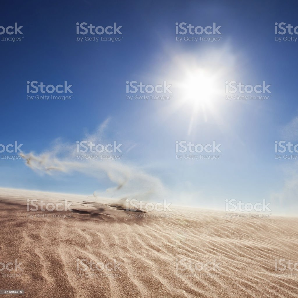 Sand Dunes at Sunrise with Swirling Sand in Air stock photo