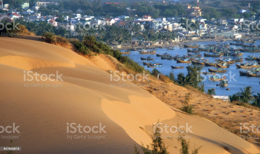 Sand dunes on a background of the bay of Mui Ne, Vietnam stock photo