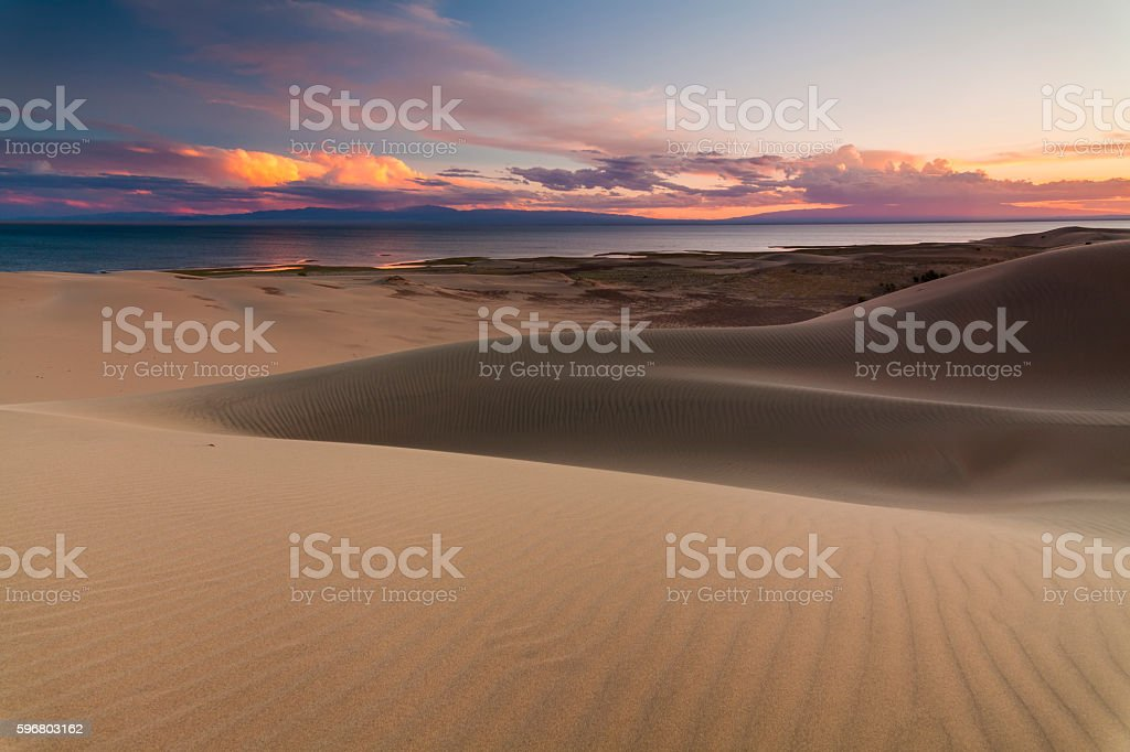 Sand dunes on the background of the desert lake. stock photo