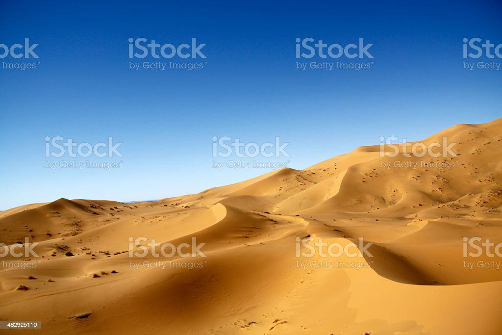 Sand dunes over the blue sky stock photo