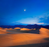 Sand dunes with a mountain scale and moon at sunset