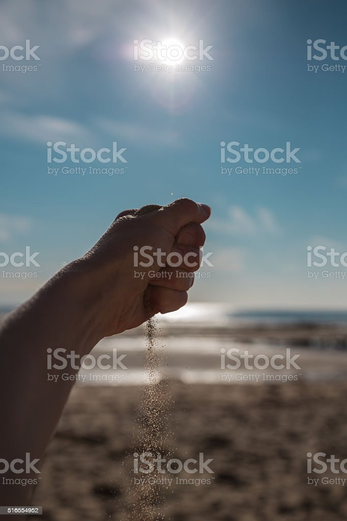 Sand falling from the hand stock photo