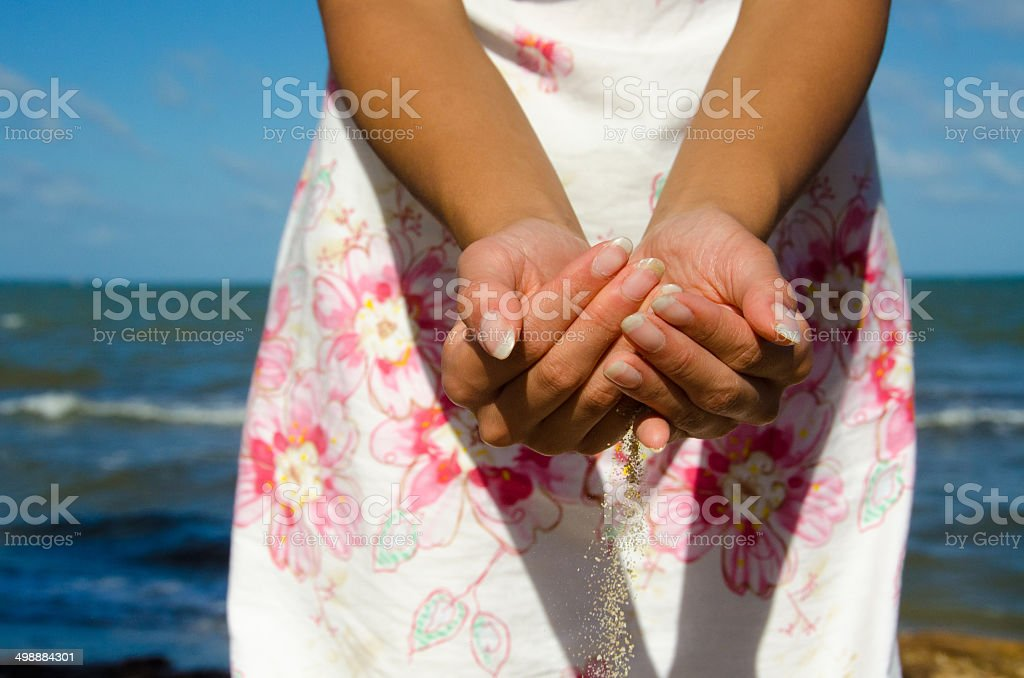 Sand flowing through the hands stock photo