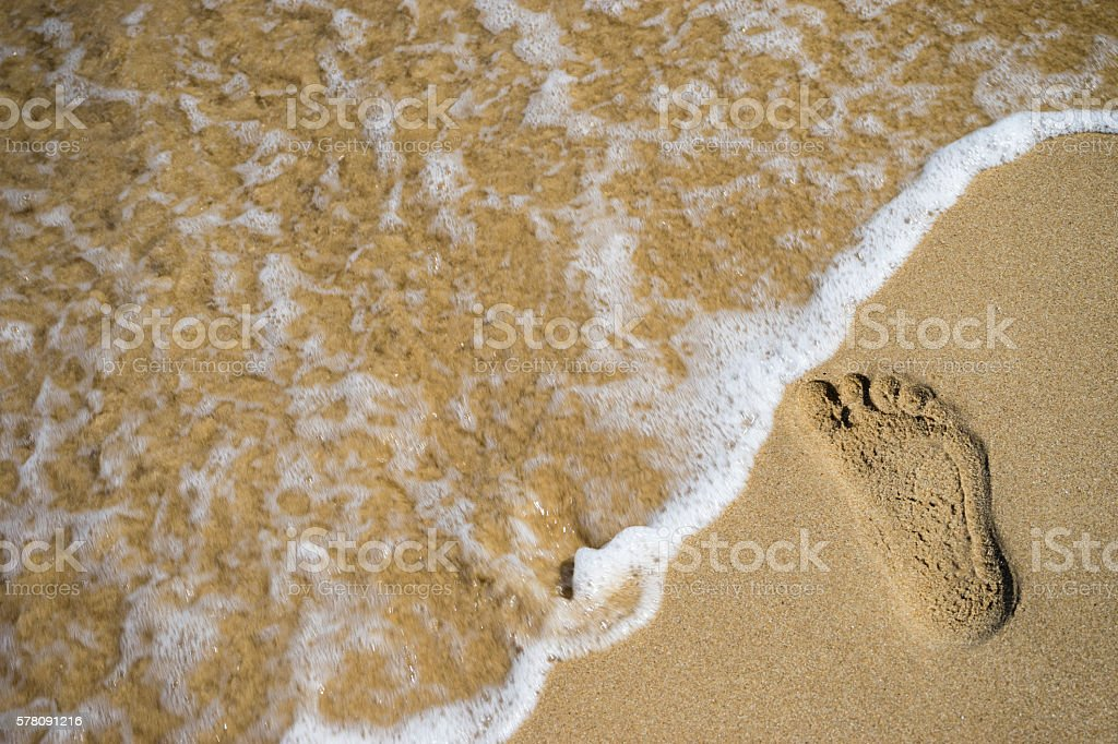 Sand footprint and wave stock photo