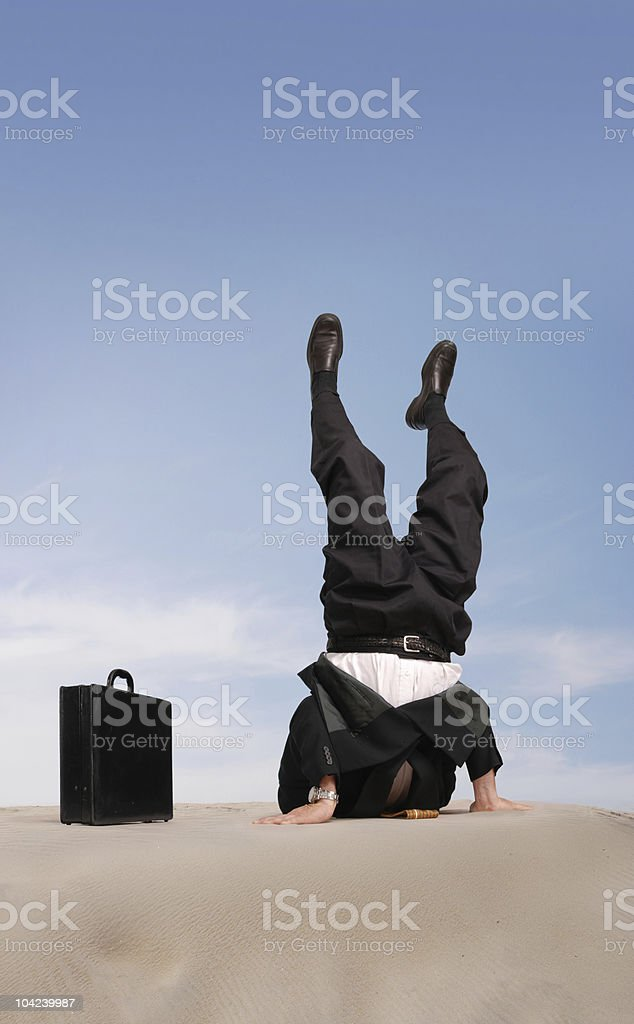 sand head stand stock photo