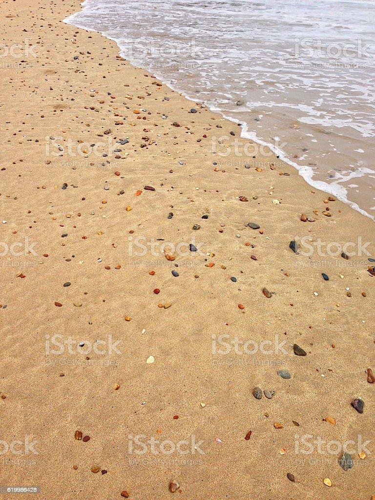 Sand on beach full of seashells, stones, pebble, waves stock photo