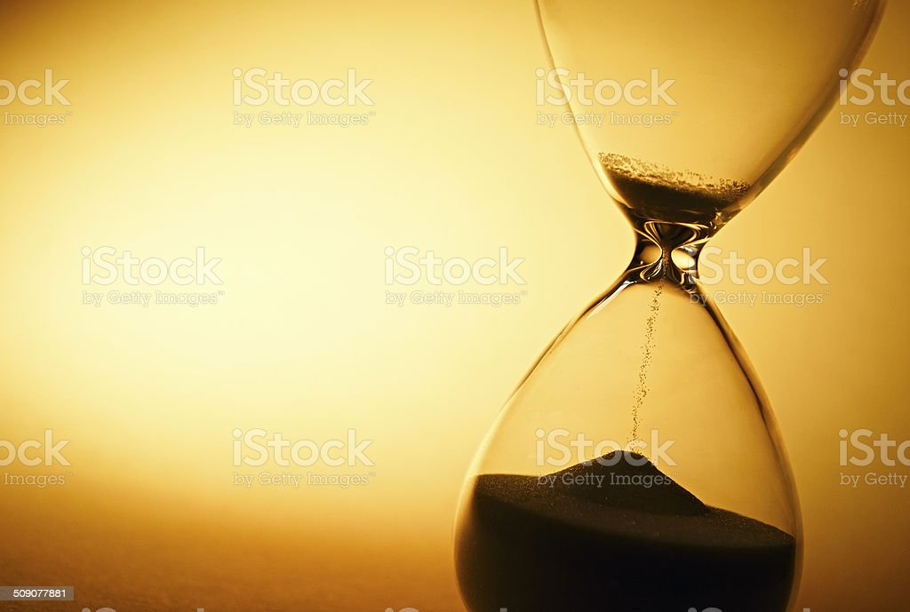 Sand passing through the bulbs of an hourglass stock photo