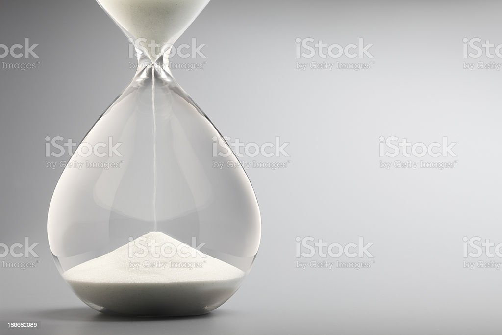 Sand Pouring Into Bottom Of Hourglass On Gray Background stock photo