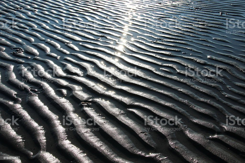 Sand ripple marks and sun reflections stock photo