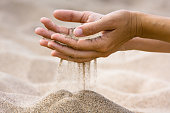 sand running through fingers of woman