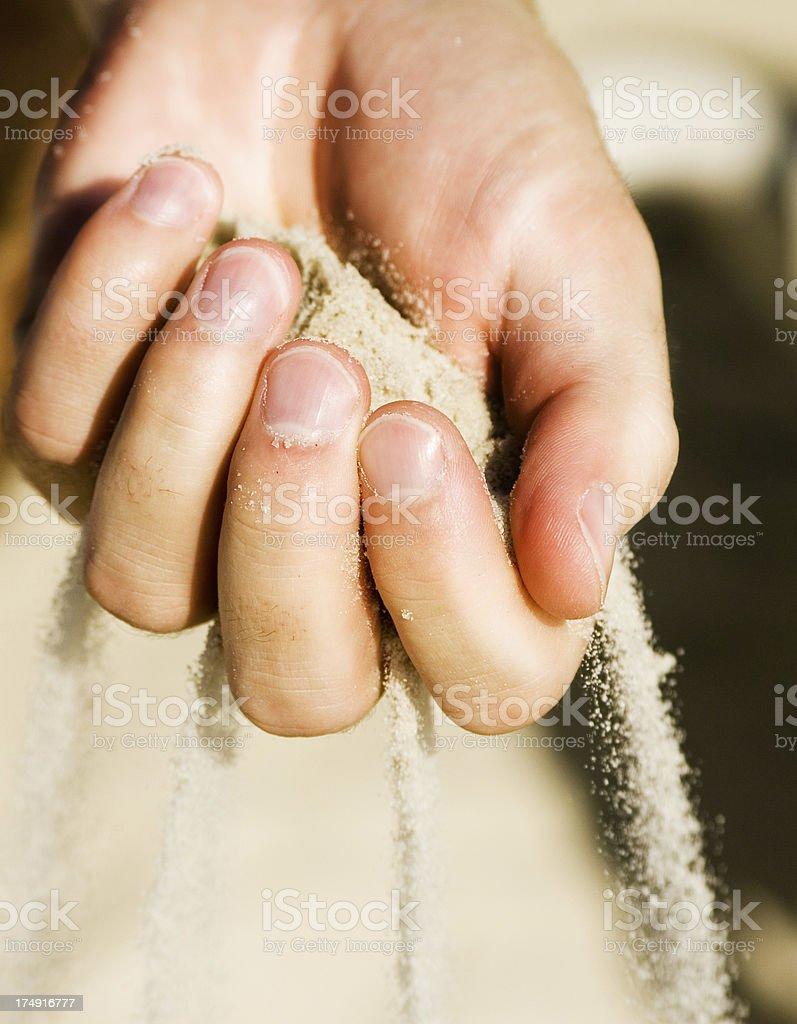 Sand running through hand stock photo
