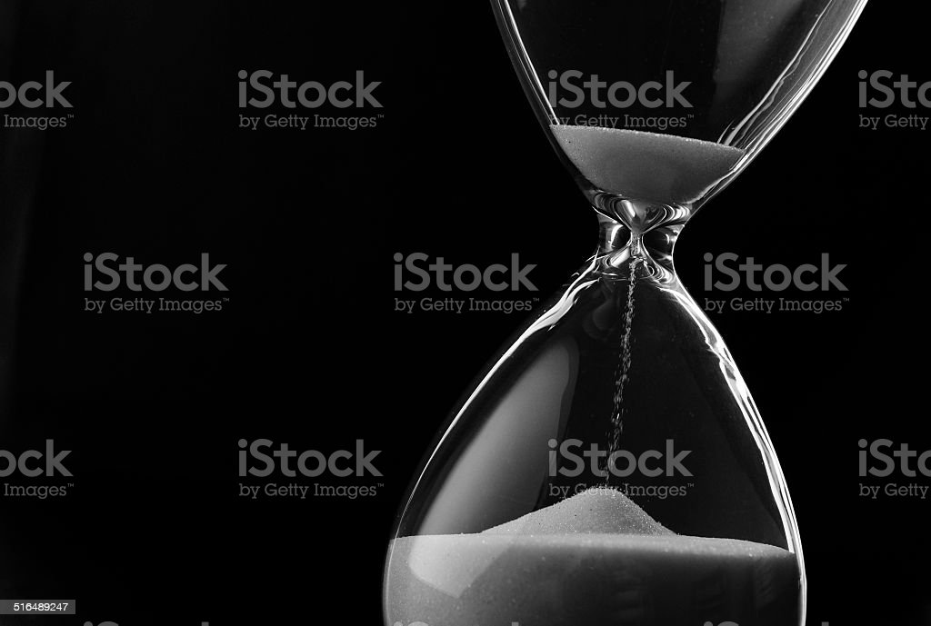 Sand running through the bulbs of an hourglass stock photo