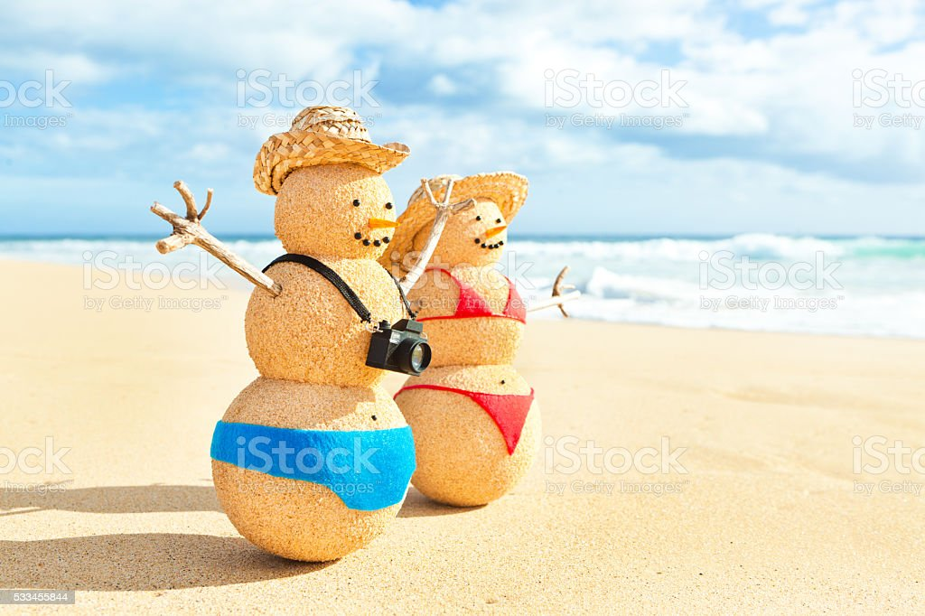 Sand Snowman Couple Winter Vacationing on Tropical Beach stock photo