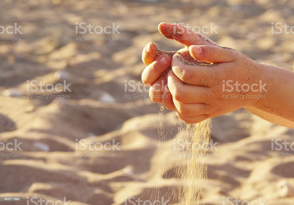 sand through fingers stock photo