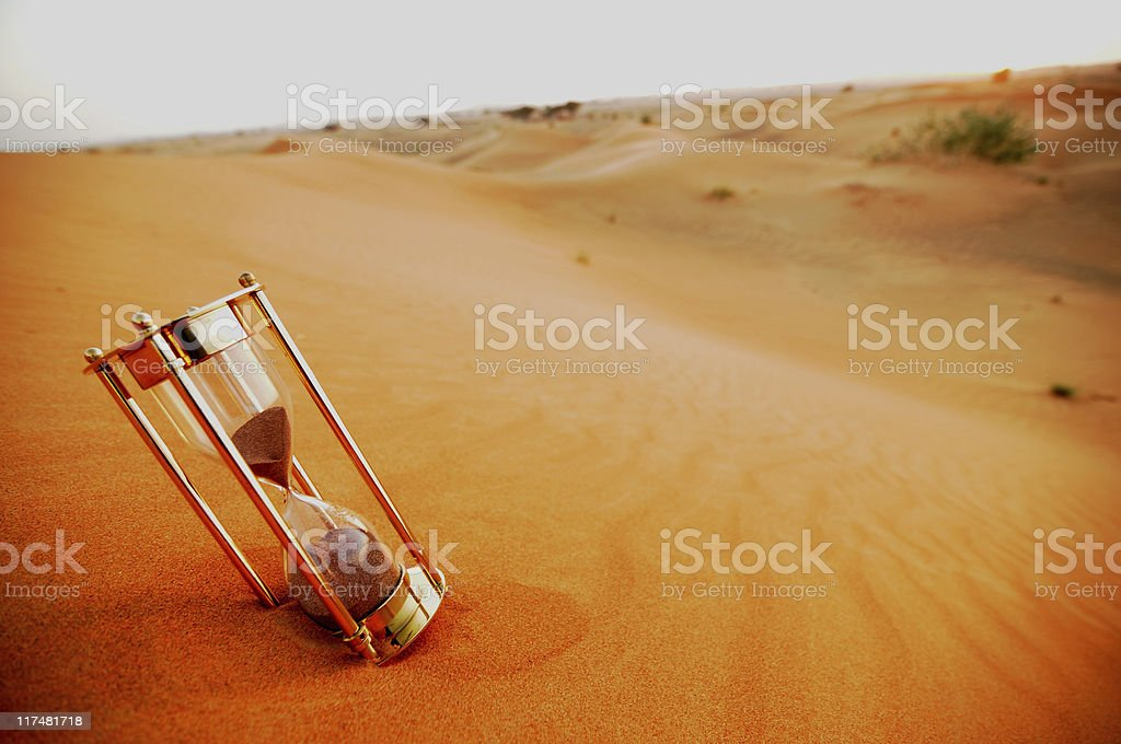 Sand timer in sand desert shows the concept of timelessness stock photo