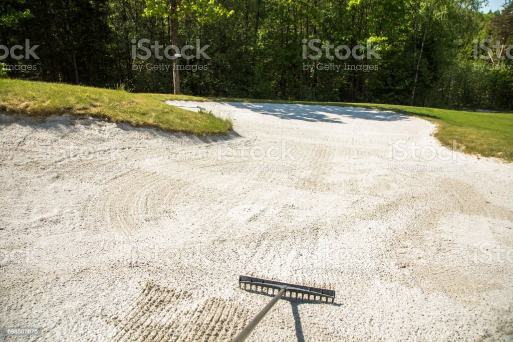 Sand trap, rake in a golf course sand bunkers, raking the sand stock photo