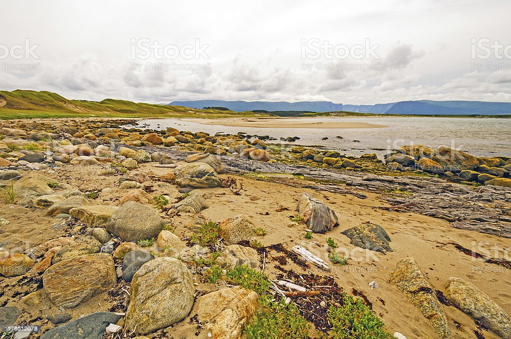 Sand with Rocks Where Ocean and River Meet stock photo