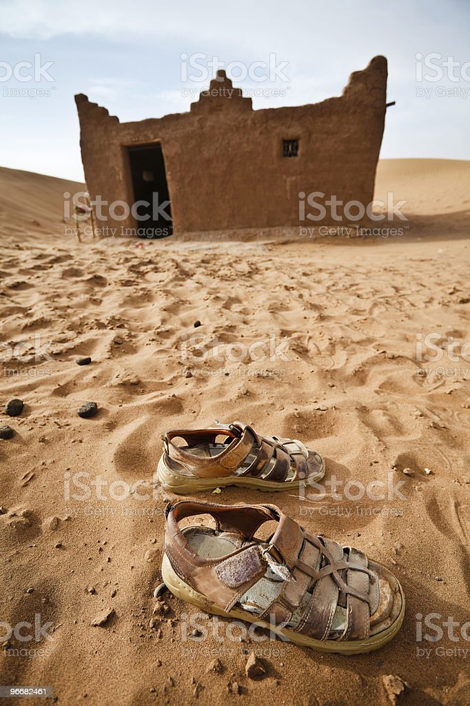 Sandals and house in Sahara desert. stock photo