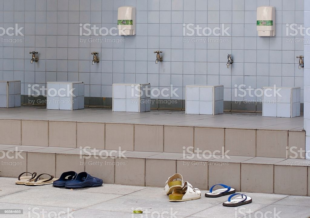 Sandals at mosque footwashing station stock photo
