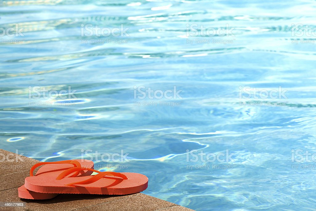 Sandals by a swimming pool stock photo