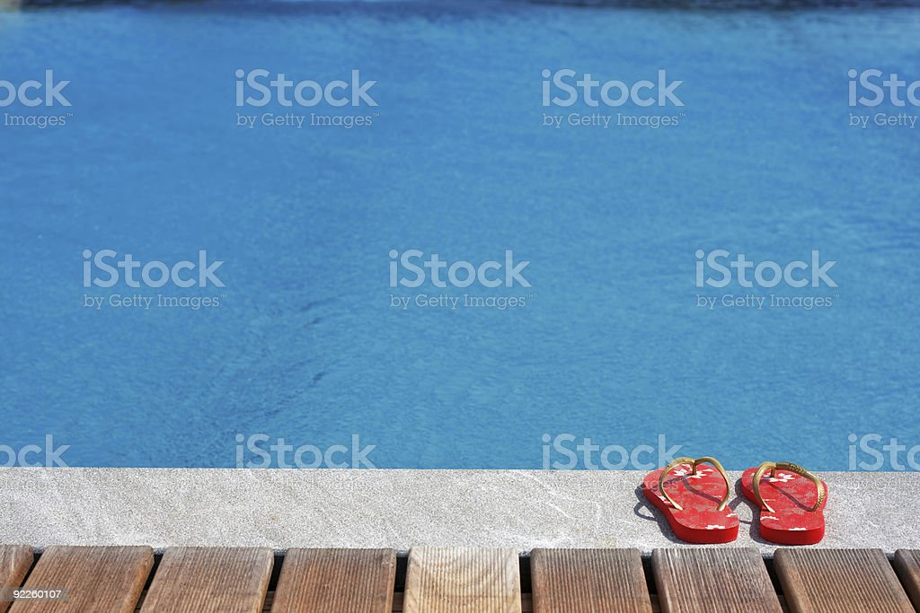 Sandals by the swimming pool stock photo