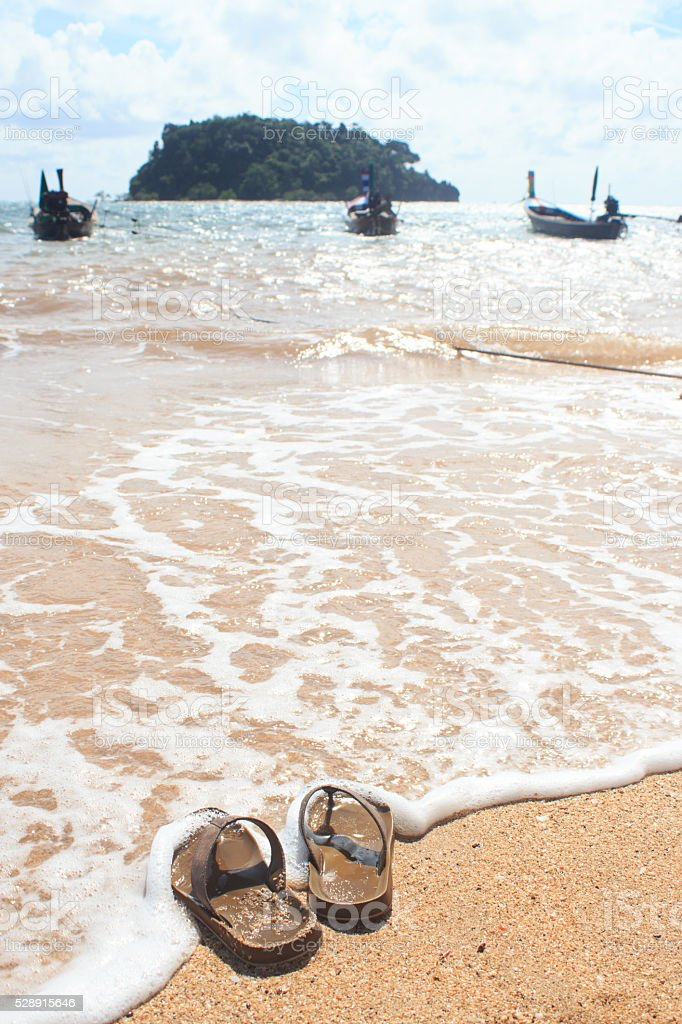 Сандалии на песчаном пляже в летнее время отдыха и отпуск. Стоковые фото Стоковая фотография