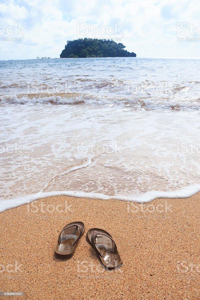 Сандалии на песчаном пляже в летнее море, отдых время отдыха Стоковые фото Стоковая фотография