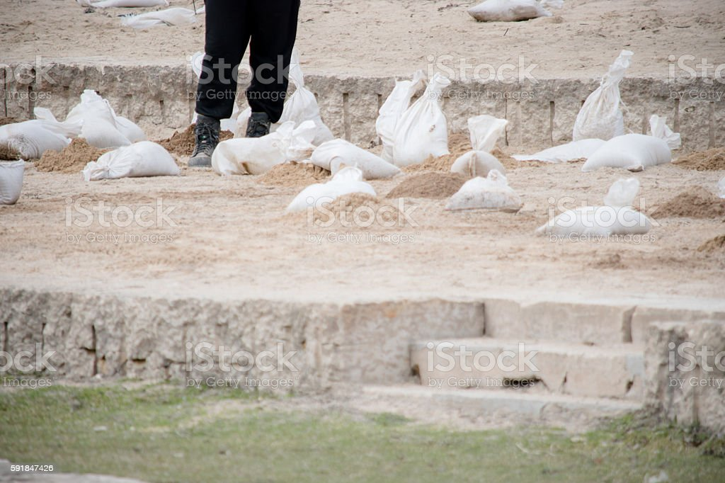 Sandbags flood prevfention and man stock photo