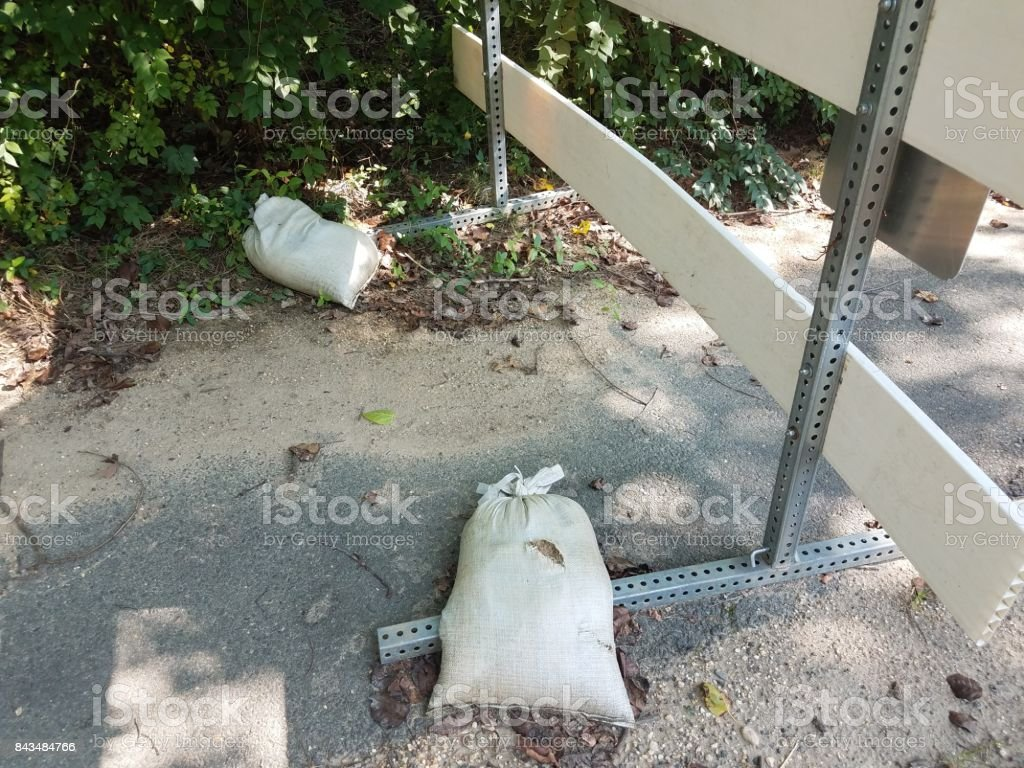 sandbags holding down a sign stock photo