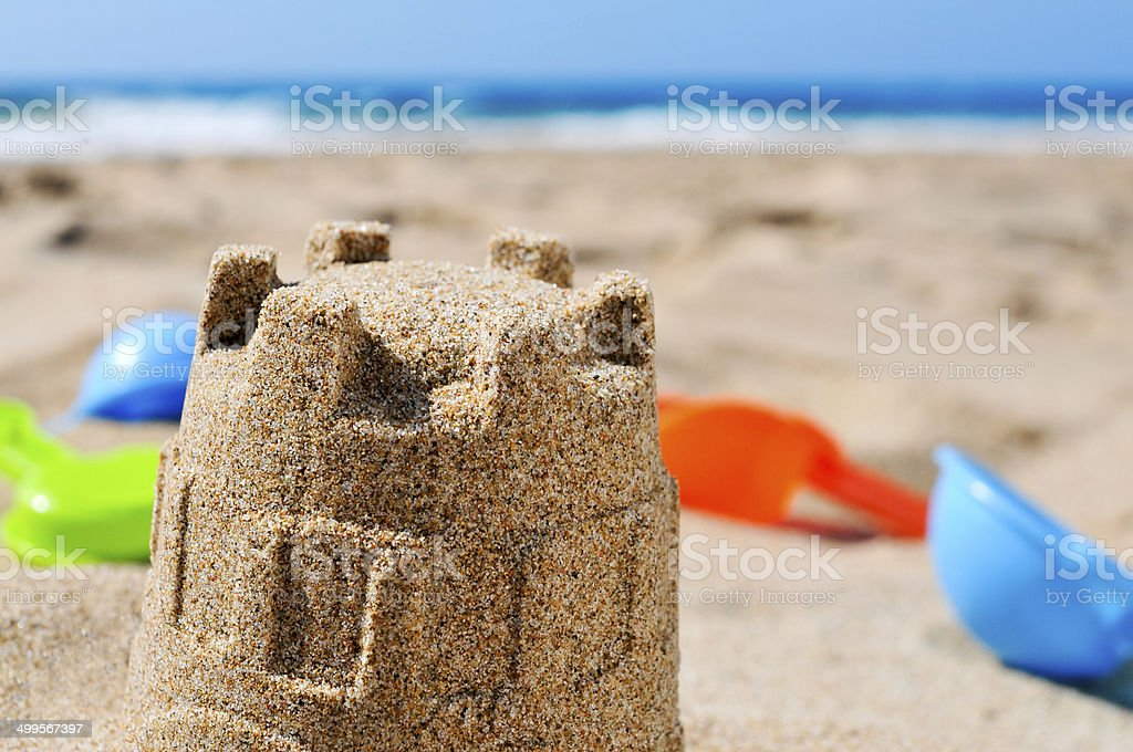 sandcastle and toy shovels on the sand of a beach stock photo