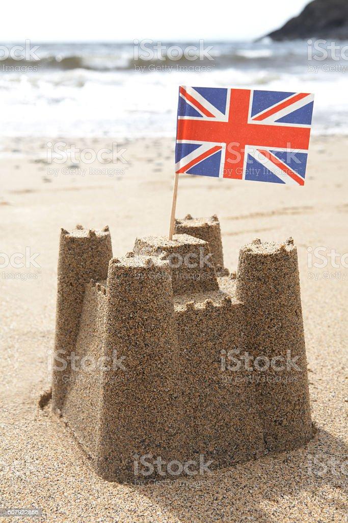 Sandcastle On Beach With Union Jack Flag stock photo