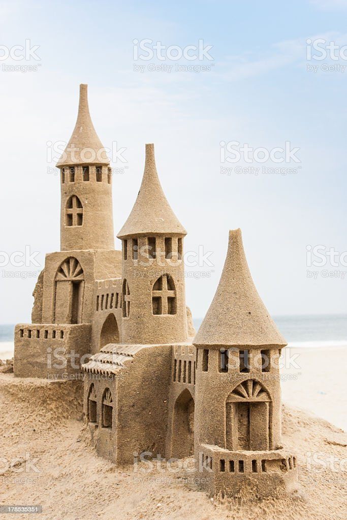 A sandcastle on the beach with windows and three turrets stock photo