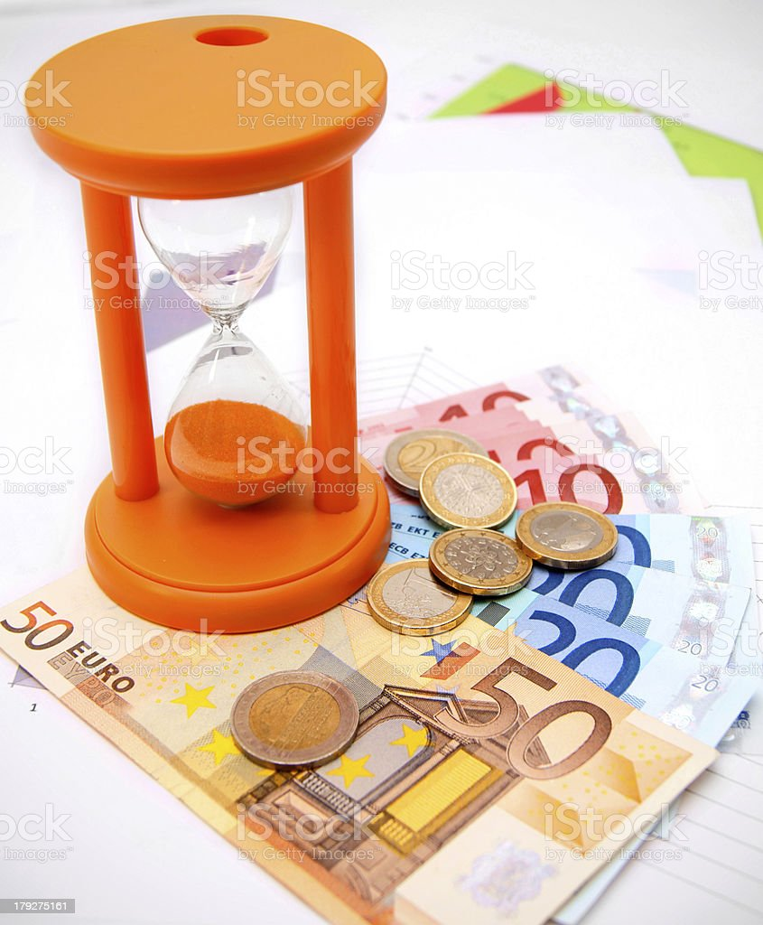 Sand-glass, coins and euro on graphs. royalty-free stock photo